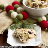 Cranberry Pistachio White Chocolate Shortbread on a white plate with a cedar sprig to garnish