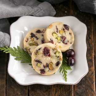 3 Cranberry Pistachio White Chocolate Shortbread Cookies on a square white plate