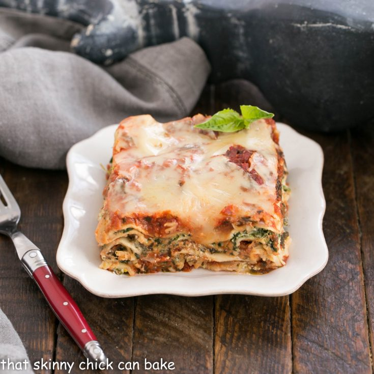 A slice of spinach lasagna on a white plate with a red handled fork