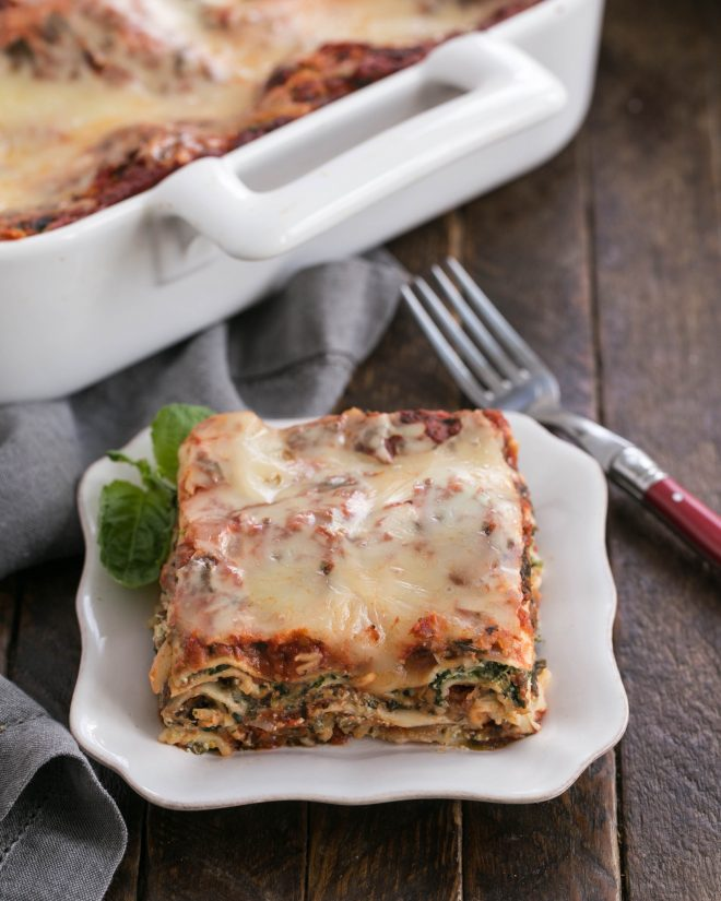 One slice of spinach lasagna on a white plate in front of the casserole dish