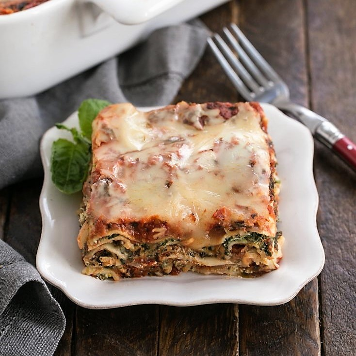 Spinach lasagna slice on a white plate