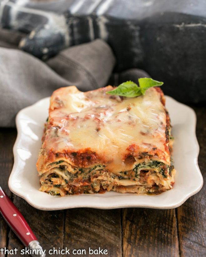 Slice of spinach lasagna on a square white plate