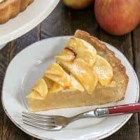 Slice of Frenh apple tart ona round white plate
