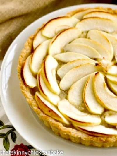 Close view of half a French Apple Tart on a white plate