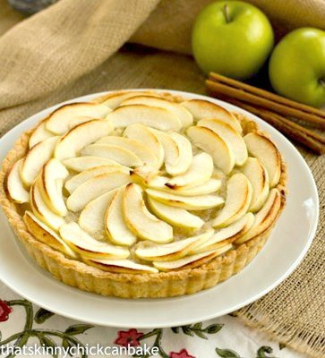 French Apple Tart on a white serving plate with some apples and cinnamon sticks in the background