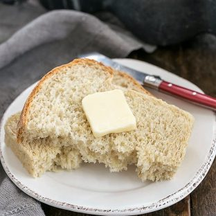 Slice of oatmeal bread torn in half and topped with butter on a round white plate with a red handled butter knife