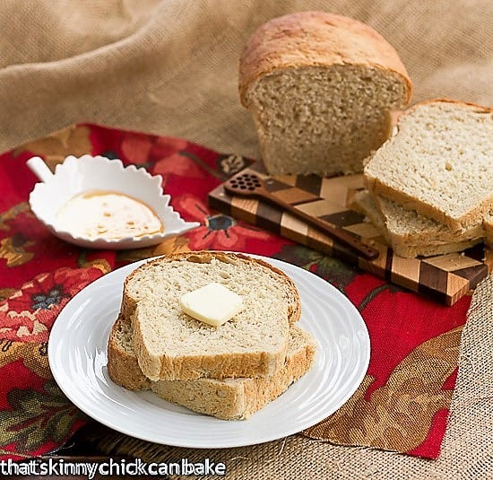 Two Slices of Classic Oatmeal Bread on a white plate topped with a pat of butter with the cut loaf on a cutting board in the background