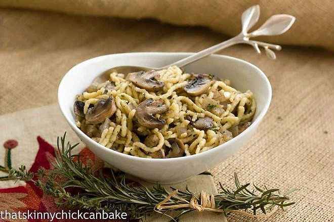 Herbed spaetzle with mushrooms in a white serving dish with a spoon