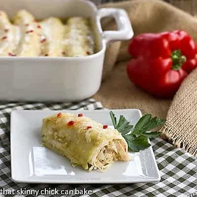 Creamy chicken enchilada on a white plate with a casserole dish in the background