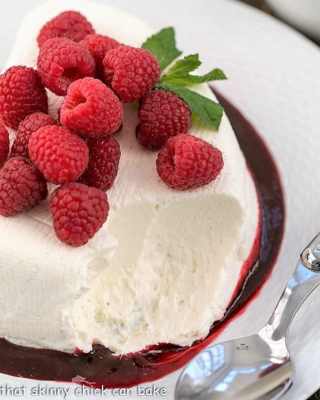 No-Bake cheesecake recipe topped with fresh raspberries with a scoop removed