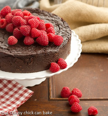 Flourless Chocolate Kahlua Cake on a white cake stand topped with fresh raspberries