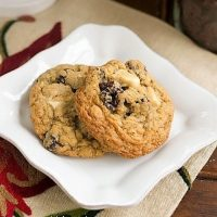 Two Oatmeal, Dried Cherry and White Chocolate Chunk Cookies on a square white plate