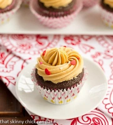 A chocolate cupcake with a swirl of caramelized white chocolate ganache on a small white plate