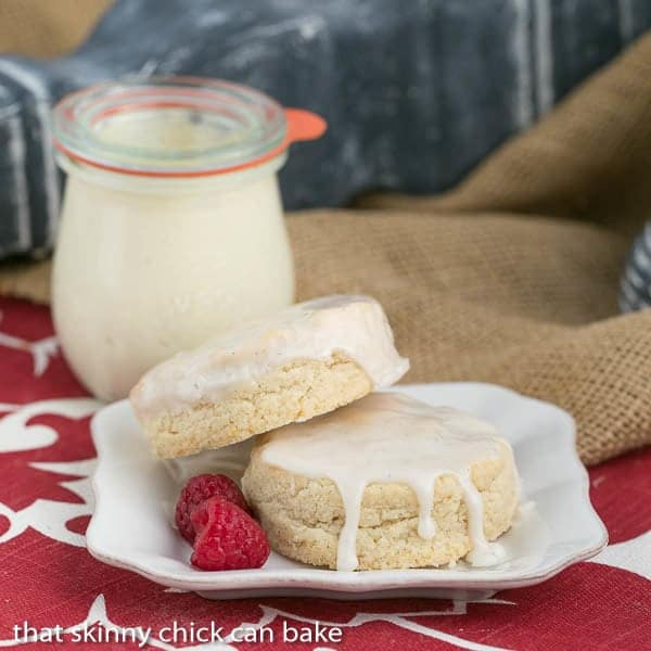 Super moist Vanilla Bean Scones on a white plate with a jar of clotted cream