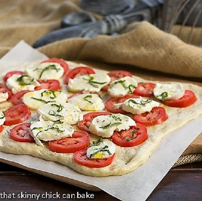 Uncooked classic pizza dough with toppings ready for the oven