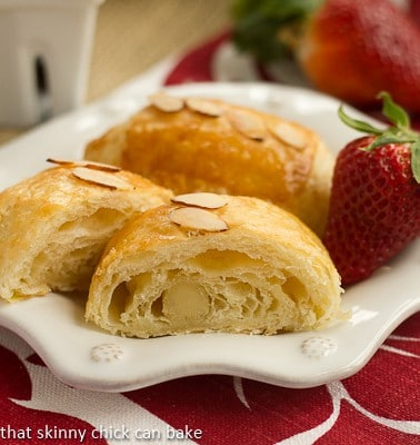 Homemade Almond Croissants on a white decorative plate with a strawberry