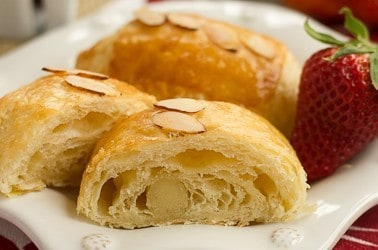 Almond croissants on a white plate with a fresh strawberry