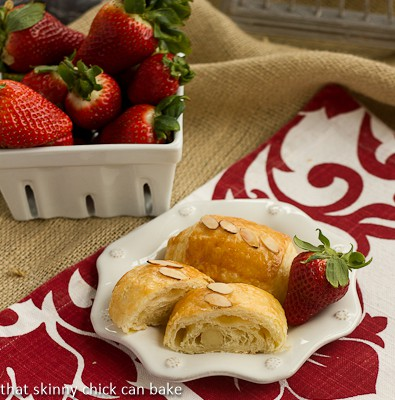 Almond croissants on a white plate on a red and white napkin with a bowl of fresh strawberries