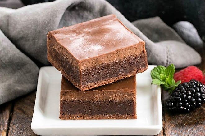 2 chocolate cheesecake brownies on a small white ceramic plate