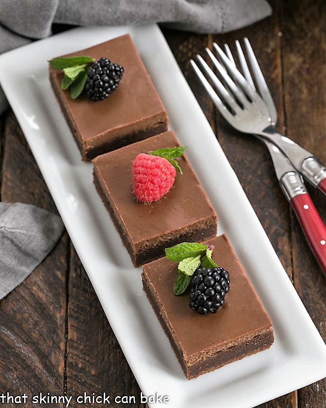 Ovehead view of 3 cheesecake brownies on a white tray topped with fresh berries