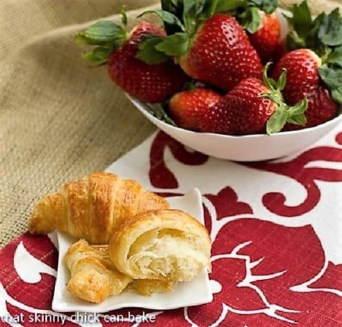 Homemade Classic Croissants with one broken open on a white plate with strawberries