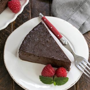 Flourless Chocolate Kahlua Cake slice on a white plate garnished with raspberries