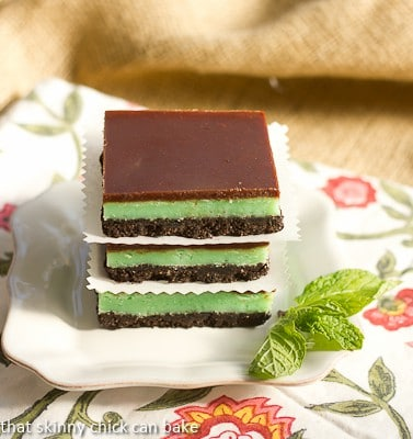 A stack of grasshopper bars on a square white plate with a sprig of mint