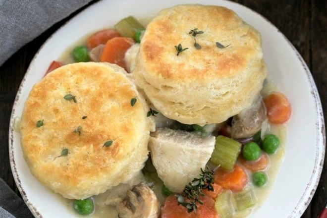 Overhead view of chicken pot pie topped with biscuits on a white plate