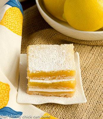 A stack of lemon squares on a square white plate