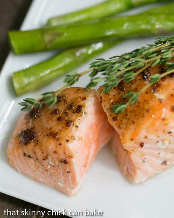 Maple Mustard Glazed Salmon with the center exposed on a white plate topped with fresh thyme
