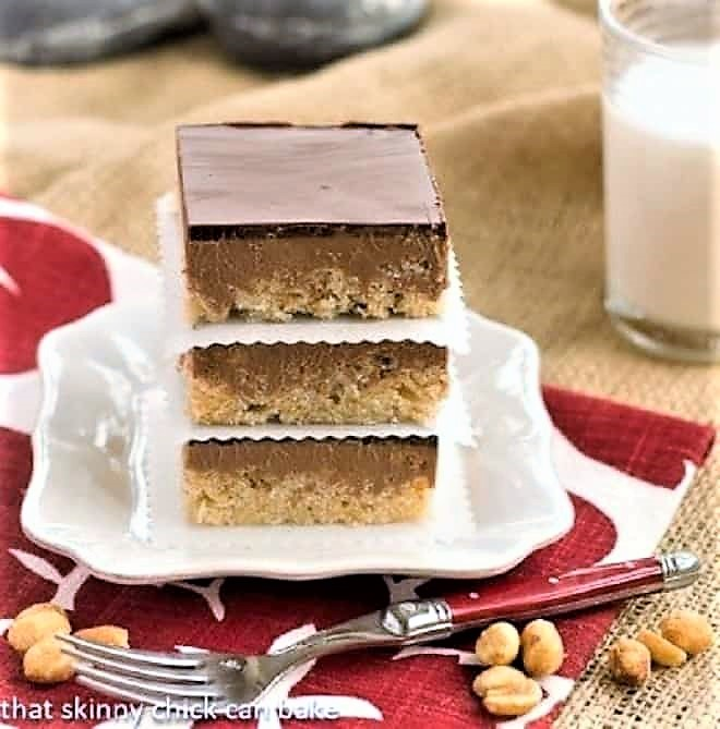 A stack of chocolate peanut butter krispie bars on a white plate over a red and white napkin