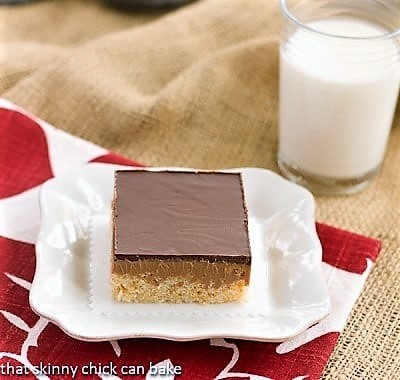 One Peanut Butter Rice Krispie Bar on a white plate with a glass of milk