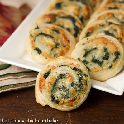 Spinach pinwheels on a white ceramic tray