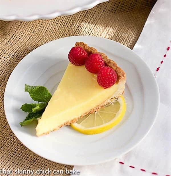 A slice of Tarte au Citron AKA French Lemon Tart garnished with raspberries