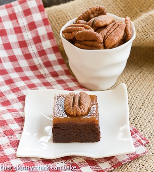 Turtle Brownies on a square white plate on a checkered napkin