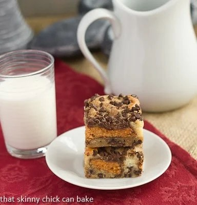 Chocolate Chip Butterfinger Cheesecake Bars stacked on a small white plate