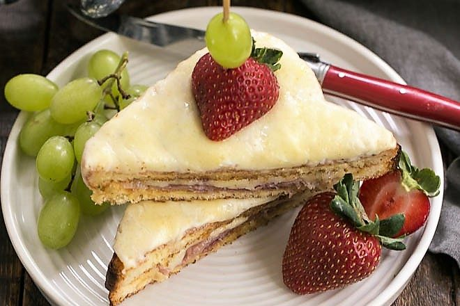 Croque-Monsieur Sandwich sliced and stacked on a white plate with grapes and strawberries