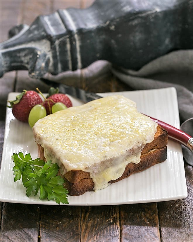 A Croque Monsieur on a white plate with a red handled knife
