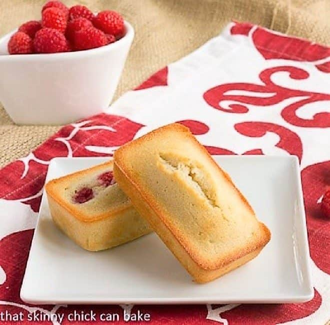 Vanilla Financiers with Raspberries on a square white plate