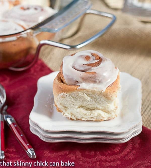 Moomie's Cinnamon Buns on a stack of small white plates with red handle forks