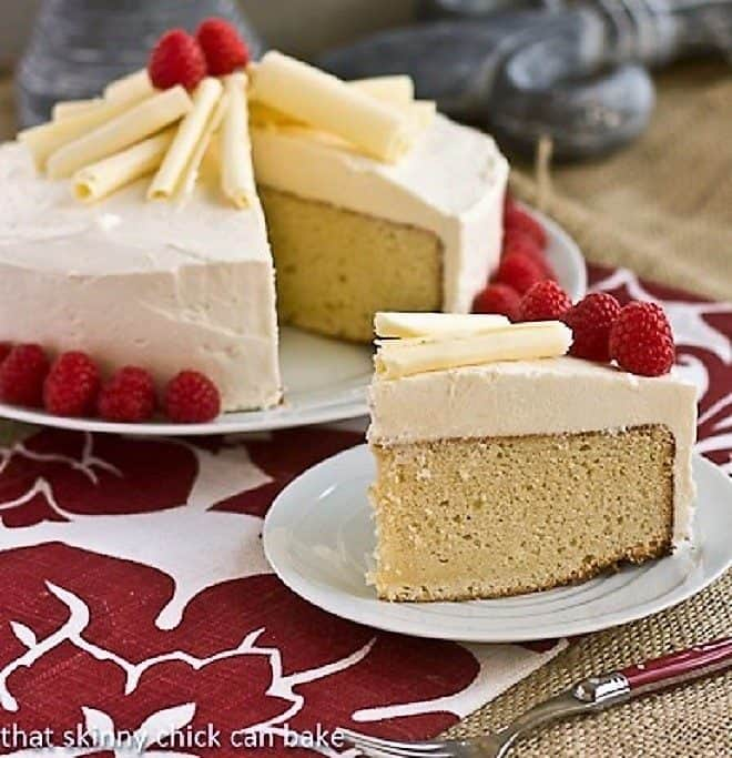 Vanilla Cake with White Chocolate Buttercream on a white cake plate with one slice in the foreground