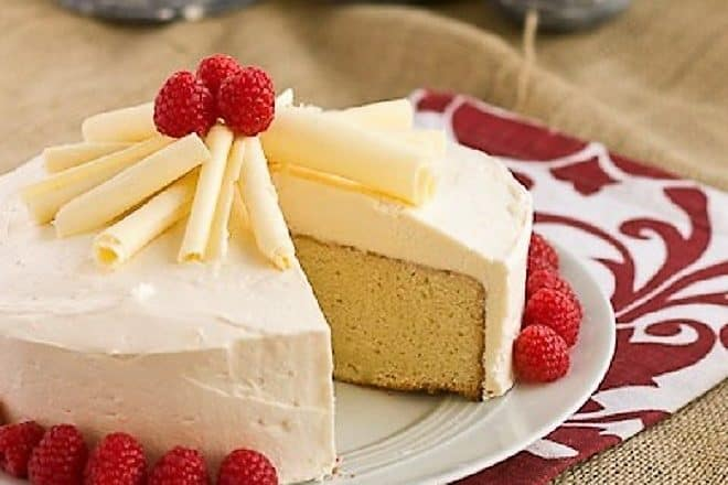Vanilla Cake with White Chocolate Buttercream on a white cake plate with a slice removed