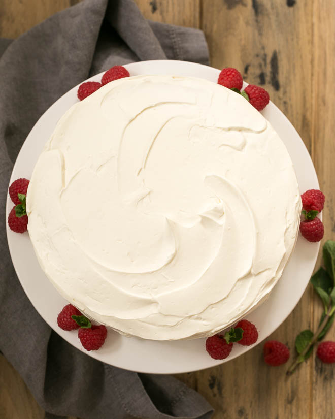 Overhead view of vanilla cake on a white cake stand with raspberries and mint