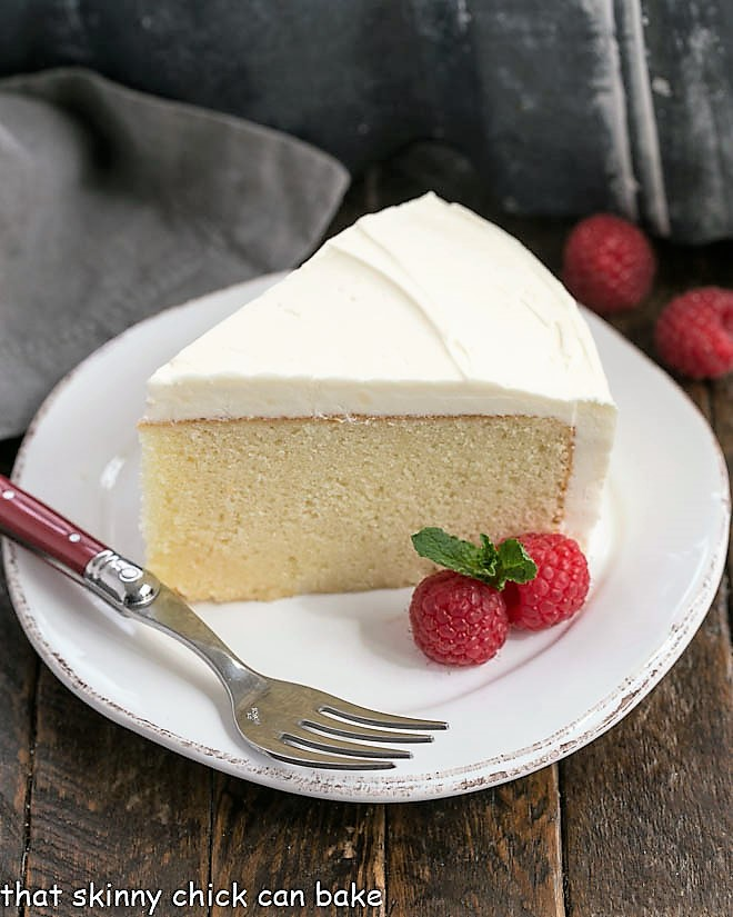A slice of this white cake recipe on a white dessert plate with a red handled fork and raspberry garnish