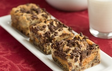 Butterfinger cheesecake bars on a white tray over a red napkin