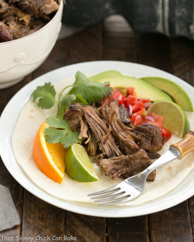 Slow cooked Pork Carnitas on a white plate with tomatoes, avocadoes and citrus