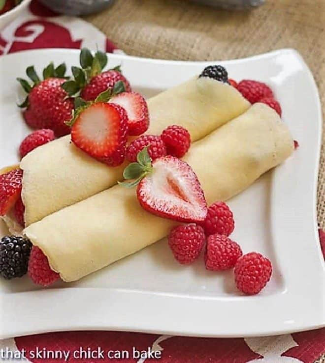 Two Brown Butter Crêpes with Berry and Cheesecake Filling topped with strawberry slices and fresh raspberries