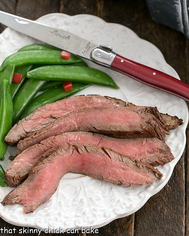 Overhead view of slices of flank steak, sugar snapped peas and a red handle knife