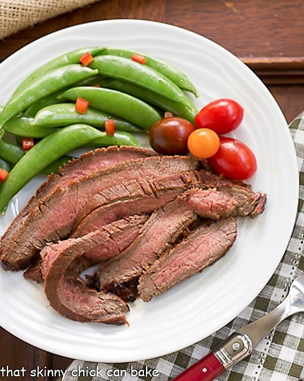 Korean Beef Recipe sliced and plated with sugar snap peas and tomatoes