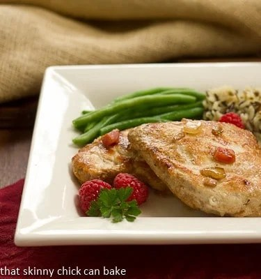 A white plate with two raspberry chicken breasts, garnished with fresh raspberries
